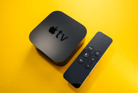 Paris, France - Nov 16, 2018: Side view from above at new black Apple TV 4K media streaming by Apple Computers  against yellow background - tilt-shift lens used 報道画像