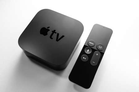 Paris, France - Nov 16, 2018: View from above at new black Apple TV 4K media streaming by Apple Computers  against white background - tilt-shift lens used