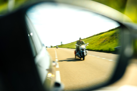 Refocused view of motorcyclist in the rear view mirror of a car driving fast on French highway