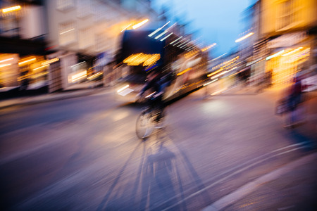 Abstract defocused light-trails of fast cyclist silhouette delivering food ordered through mobile app - fast double-decker bus behind Stockfoto