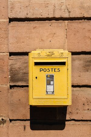Bergheim, France - 19 Apr 2019: Old vintage French La Poste mailbox painted in yellow color seen on the walls of Bergheim city-hall
