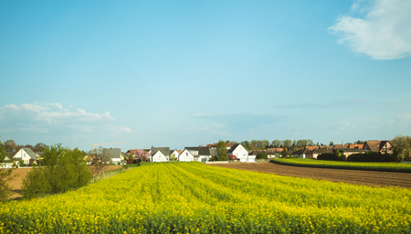 Typical French village of Benfeld with multiple houses, large area of plowed fields, raps in bloom fields and clear blue sky with some clouds Stock Photo