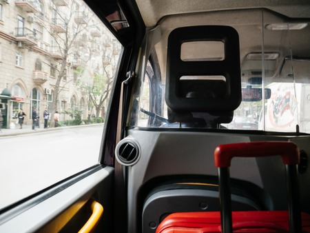 Defocused view from hackney carriage taxi cab in Baku Azerbaijan with red luggage inside and street view with people silhouette