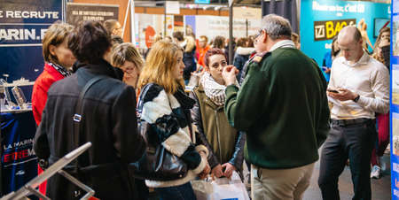 STRASBOURG, FRANCE - FEB 4, 2016: Girls of all ages attending annual Education Fair to choose career path and receive vocational counseling - French Army recruiting girls senior man explaining things Editorial