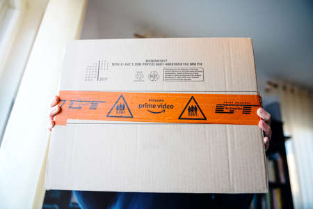 Paris, France - MAr 16, 2019: Woman with Amazon Prime Video icon on the cardboard box carton parcel with red security sealing tape membership streaming service and Prime Original The Grand Tour