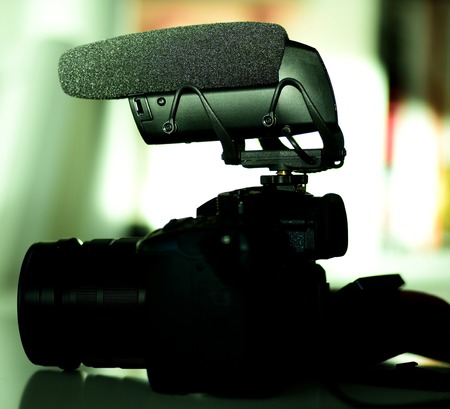 Detailed photograph of new microphone mounted on small mirrorless camera - green color cast 免版税图像