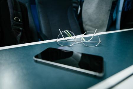 Focus on titanium eyewear glasses with new modern smartphone on train table inside British train