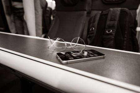 Focus on titanium eyewear glasses with new modern smartphone on train table inside British train black and white