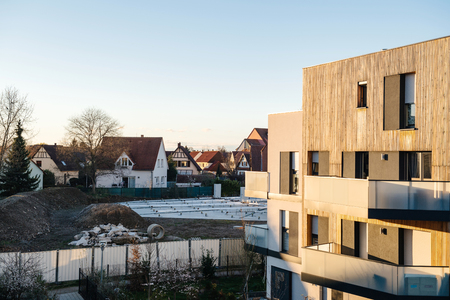 Elevated view of new building apartment houses made from ecological wood at sunset with new constructions sites started in background