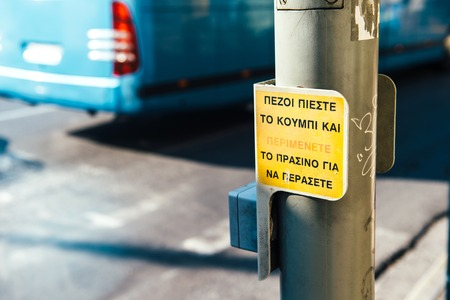 Greek street crossing with text attention to the passing vehicles