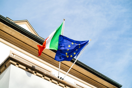 Low angle view of The European flag of Europe and Italian flag waving in wind official delegation embassy consulate