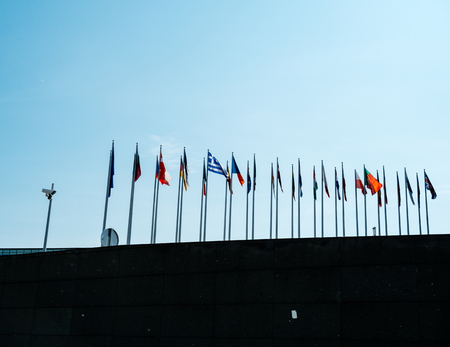 Side view of European union member flags waving and surveillance CCTV camera in front of the Parliament days before Parliamentary elections on 26 may