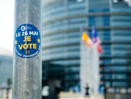 Strasbourg, France - May 23, 2019: I vote sticker on street sign pole with all European union member states flags waving in front of the building 2019 European Parliament election Stock Photo