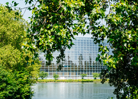 Wide facade of European Parliament View through trees of headquarter in Strasbourg a day before 2019 European Parliament election - clear blue sky and calm Ill river water.