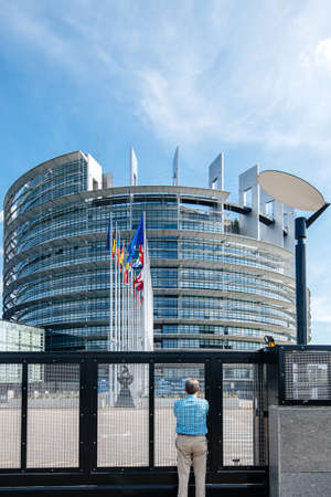 Strasbourg, France - May 26, 2019: Seniopr man admiring through the closed gate of the European Parliament headquarter with all European Union flags waving - clear blue sky in background