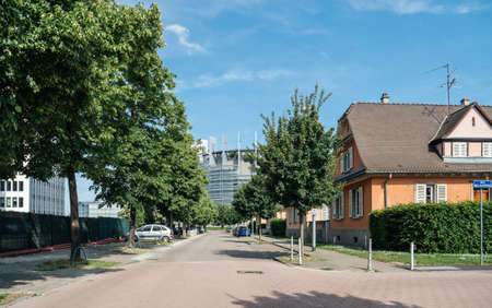 Strasbourg, France - May 26, 2019: European Parliament headquarter as seen from Allee du Printemps street with tall trees and parked cars