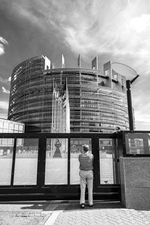 Strasbourg, France - May 26, 2019: Seniopr man taking photograph through the closed gate of the European Parliament headquarter with all European Union flags waving - black and white