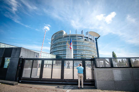 Strasbourg, France - May 26, 2019: Seniopr man taking photograph through the closed gate of the European Parliament headquarter with all European Union flags waving - clear blue sky in background horizontal image