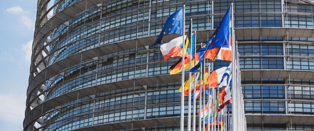 Wide image of flags all member states of the European Union waving in calm wind in front of the Parliament headquarter on the day of 2019 European Parliament election.