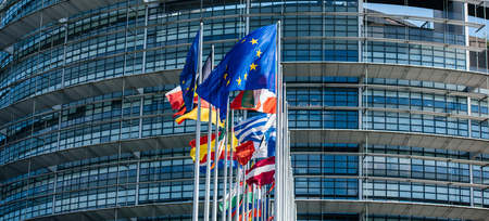 Wide image flags of all member states of the European Union waving in calm wind in front of the Parliament headquarter on the day of 2019 European Parliament election. Stock Photo