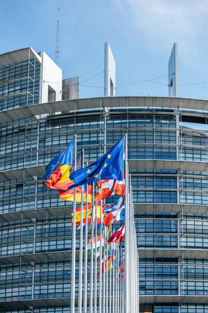 Flaggen aller Mitgliedsstaaten der Europäischen Union wehten am Tag der Wahlen zum Europäischen Parlament 2019 bei ruhigem Wind vor dem Parlamentssitz mit strahlend blauem Himmel im Hintergrund.