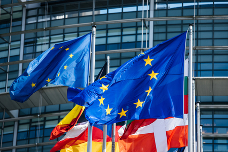 Detail of flags of all member states of the European Union waving in calm wind in front of the Parliament headquarter on the day of 2019 European Parliament election.
