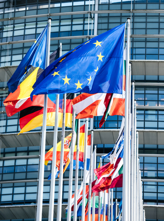 Clean flags of all member states of the European Union waving in calm wind in front of the Parliament headquarter on the day of 2019 European Parliament election. Stock Photo