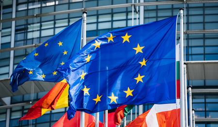 Flags of all member states of the European Union waving in calm wind in front of the Parliament headquarter on the day of 2019 European Parliament election.