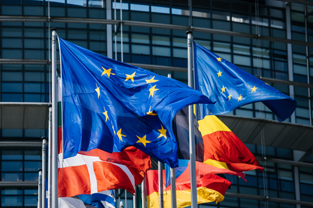 Close-up of flags of all member states of the European Union waving in calm wind in front of the Parliament headquarter on the day of 2019 European Parliament election