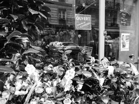 Paris, France - Jan 30, 2018: French florist store facade view from the street selling diverse type of bouquets flowers - black and white