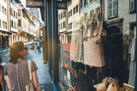 Strasbourg, France - Jul 22, 2017: Rear view of beautiful young woman in French city admiring current sales soldes offers in clothes fashion store