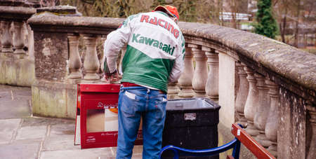 Oxford, United Kingdom - Mar 3, 3017: Homeless person searching for food in public garbage waste bin