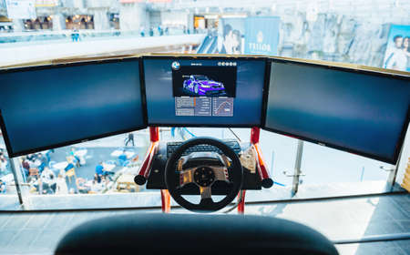Bucharest, Romania - 2016: Triple screen setup with steering wheel and pedals installed on racing chair inside Bucharest Mall - Racing games for customers