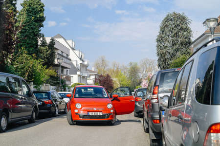 Strasbourg, France - Apr 4, 2017: Fiat 500 red car with open door blocking entire street in Strasbourg in residential area