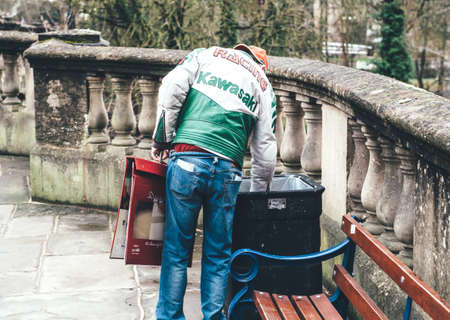 Oxford, United Kingdom - Mar 3, 3017: Rear view of homeless person wearing Racing Kawasaki leather vest searching for food in public garbage waste bin