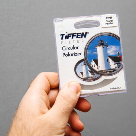 Paris, France - Jan 3, 2018: Man hand holding against gray background professional Tiffen Circular Polarizer filter for 77mm diameter camera lens Editorial