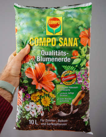 Frankfurt, Germany - Apr 22, 2019: Man hand holding against gray background package of COMPO SANA Qualitats-Blumenerde quality soil for indoor outdoor plants Editorial