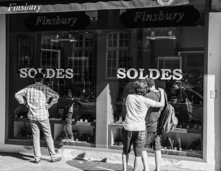Strasbourg, France - Jul 22, 2017: Rear view of customers looking at the showcase windows of large stores in city center during sale soldes season promotion period at Finsbury shoes store - black and white Editorial