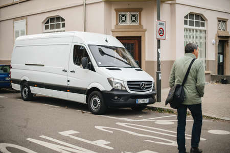 Strasbourg, France - Apr 5, 2017: Adult man crossing street in front of white Mercedes-Benz Sprinter van parked on French street  - delivery van Editorial