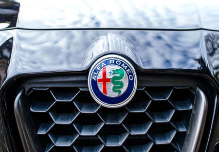 Paris, France - Feb 19, 2017: Close-up Front view of Alfa Romeo icon with red cross and dragon on the blue car Editorial