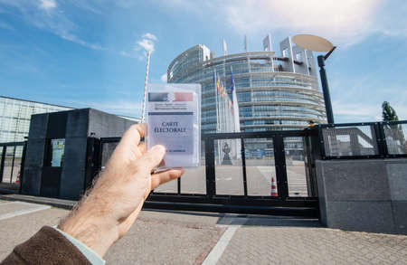 Strasbourg, France - May 26, 2019: man hand holding Voters car French Carte Electorale at the entrance of European Parliament headquarter building with all flags on the 2019 European Parliament election day