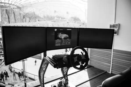 Bucharest, Romania - 2016: Triple screen setup with steering wheel and pedals installed on racing chair inside Bucharest Mall - Racing games - black and white image Editorial