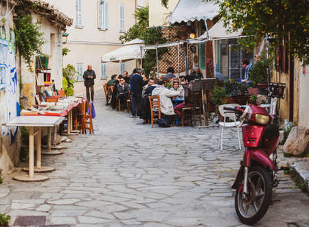 Athens, Greece - Mar 28, 2016: Tiny cute Greek street with people enjoying food on the terrace cafe in cozy vintage neighborhood Editorial