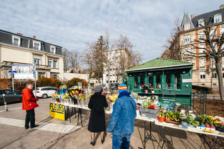 Strasbourg, France- Feb 19, 2017: People waiting at florist kiosk shop store to buy fresh spring flower as narcissus, tulips, daisies