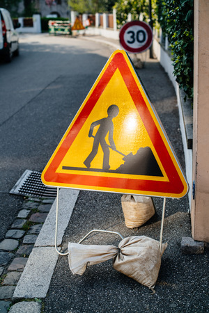 Construction roadworks warning sign on French tiny street