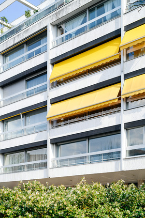 French 70s architectural style building with yellow awnings on balconies opened - covered by sun-shield on a warm summer day Фото со стока