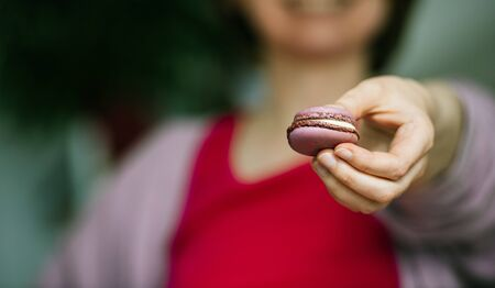Young happy French woman showing presenting delicious French sweet macaron made from violets flower