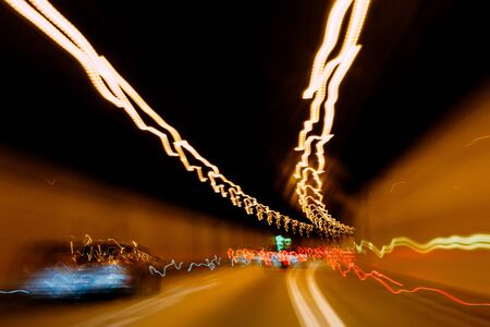 Abstract defocused view of lights of cars driving fast inside closed tunnel - security safety concept