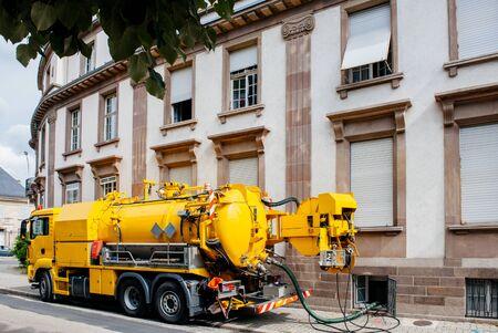 Vista lateral del potente camión de alcantarillado de aguas residuales amarillo moderno profesional que trabaja cerca de una casa bombeando agua de canalización del sótano Foto de archivo