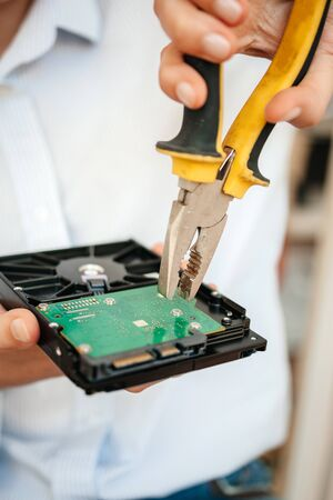 Female IT computer repair IT woman using yellow metal pliers to fix broken poor manufacture HDD disk drive disassembling the green board Banco de Imagens